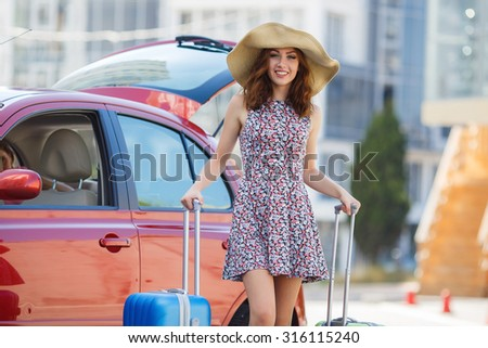 one young woman alone with suitcases. Vacation concept. Car trip. Summer vacation. girl posing with her luggage. woman traveling with suitcases, walking on the road