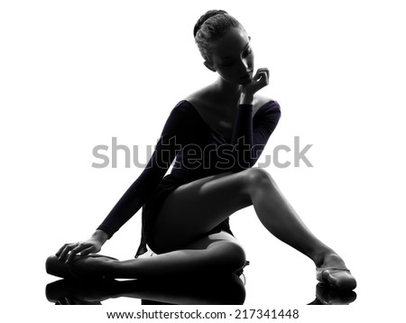 one  young woman ballerina ballet dancer stretching warming up in silhouette studio on white background - stock photo