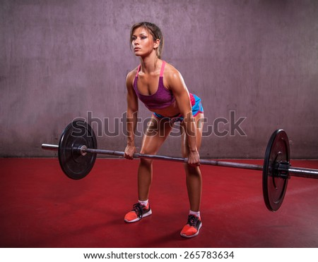 One young woman working hard in the gym.  She is lifting weights. Sport and fitness. - stock photo