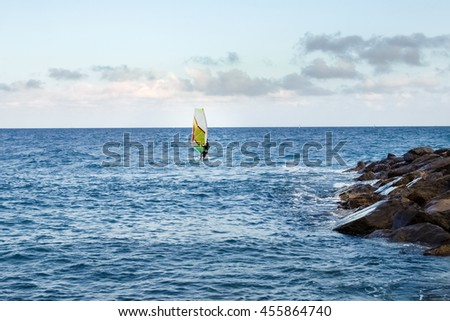 Oneglia, Italy - June 14, 2015: Windsurfing in the evening light - stock photo