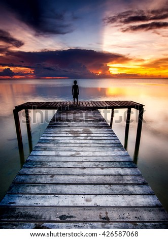 ong exposed sunset seascape at a wooden jetty in Kudat Sabah Malaysia. image contain soft focus and blur. - stock photo