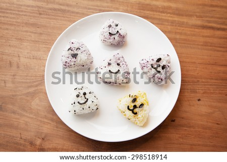Onigiri rice balls with smiley faces, made with cut out nori seaweed, on white plate.  - stock photo
