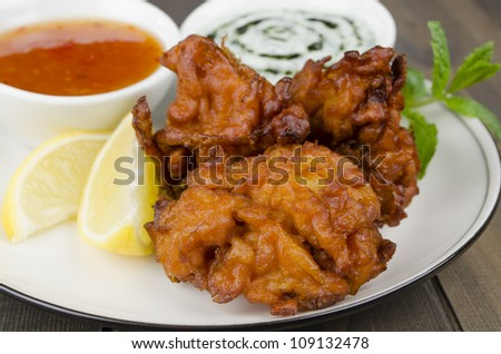 Onion Bhajis & Dips - Deep fried south asian snack with mango chutney and mint raita, garnished with mint leaves and lemon wedges on a white plate. - stock photo