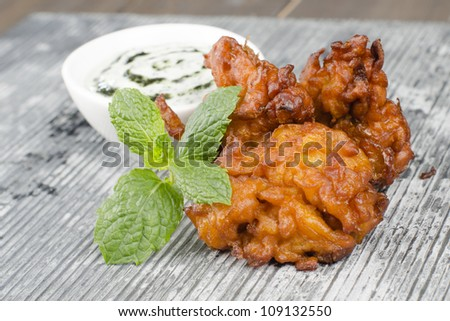 Onion Bhajis & Mint Raita - Deep fried asian snack with a yoghurt and mint dip, garnished with mint leaves on a slate. - stock photo