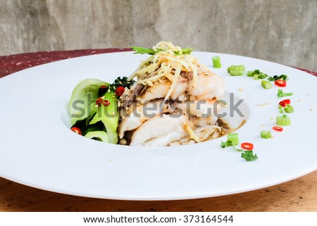 Onion Oil and Ginger Sauce Steamed Fish in chinese style.Healthy Food /Clean food.Steamed Atlantic Cod fish with spices and vegetable  - stock photo