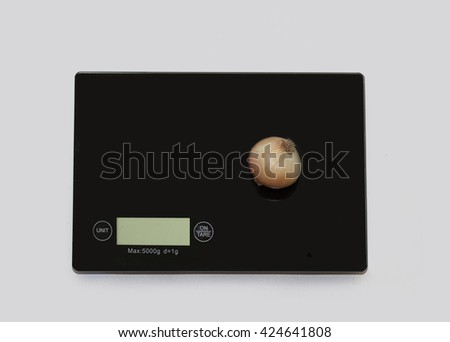 Onion on a digital white kitchen scale. (weighing products) - stock photo