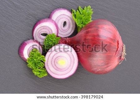 Onion. Onion rings. Onion slice. Onion,onion,onion,onion.Red onion isolated on black stone background.  Onion on black. Sliced onion with parsley. Healthy onion. Sliced Onion vegetables.  - stock photo