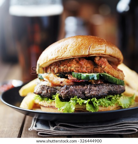 onion ring bacon barbecue burger with fries and beer shot with selective focus - stock photo