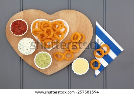Onion ring snack food with dip selection and striped napkin. - stock photo