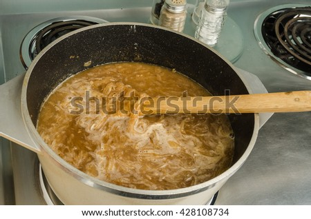 Onion Soup boiling in large pot on electric range.
