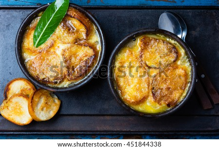 Onion soup with dried bread and cheese on clay bowls on black background. Top view - stock photo