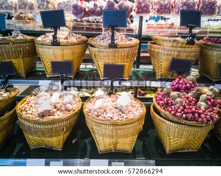 Onions and garlic in a basket for sale on the supermarket.