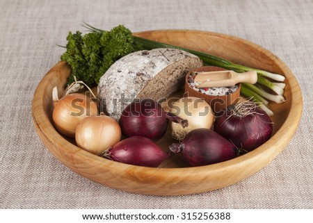 Onions, brown bread wooden tray with parsley and salt and celery. - stock photo