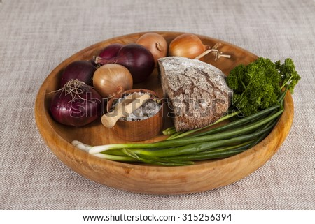 Onions, brown bread wooden tray with parsley and salt and celery.