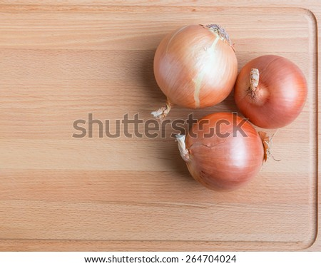 Onions on wooden cutting  board. - stock photo