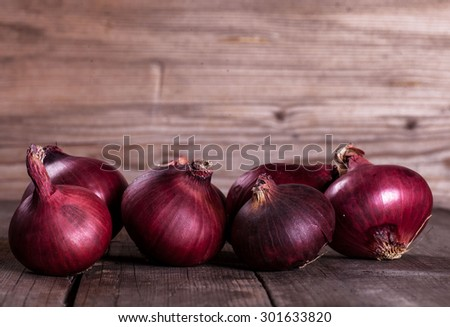 Onions on wooden table with wooden background - stock photo