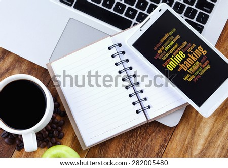 Online Banking word cloud arrangement concept on smartphone screen. Notebook,smartphone,book and a cup of coffee on wooden table. - stock photo