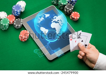 online casino, worldwide gambling, technology and people concept - close up of poker player with playing cards, tablet pc computer and chips at green casino table - stock photo