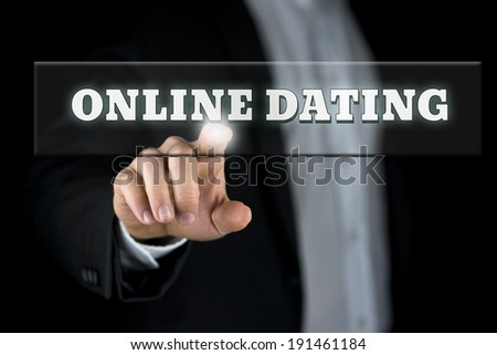 Online dating button on virtual screen with male hand activating it from behind. - stock photo