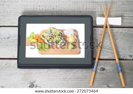 Online Japanese food delivery concept with sushi rolls on an electronic tablet and chopsticks - stock photo