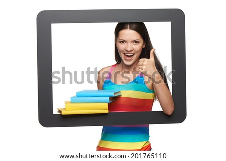 Online library concept. Happy young woman holding stack of books through tablet frame gesturing thumb up, over white background - stock photo