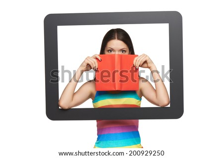 Online library concept. Happy young woman peeking over the edge of the opened book looking through tablet frame, over white background - stock photo