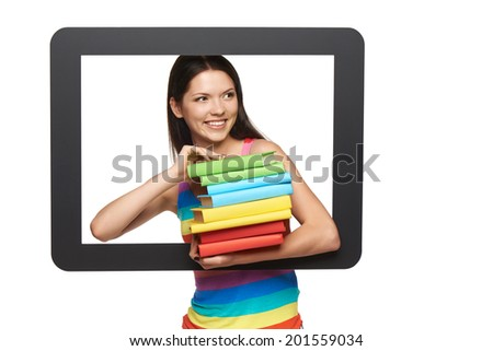Online library / learning concept. Happy young woman holding stack of books through tablet frame, looking away, over white background - stock photo