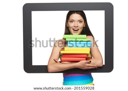 Online library / learning concept. Surprised happy young woman holding stack of books through tablet frame, over white background - stock photo