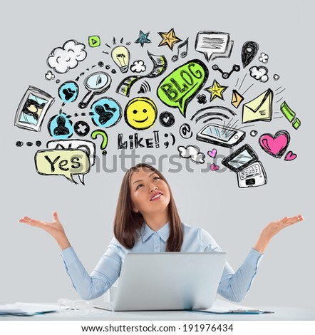 Online life concept. Business Woman looking upwards while working at office using laptop. Bright sketches overhead. - stock photo