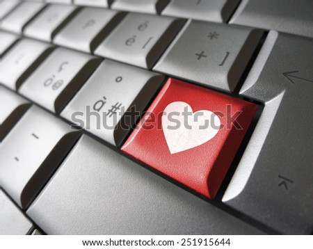 Online love and valentines lovers concept with a heart icon and symbol on a red computer key.