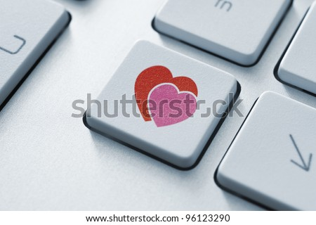 Online love button on the keyboard. Toned Image. - stock photo