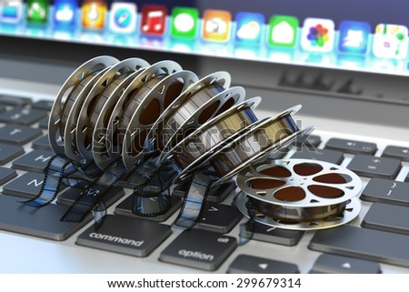 Online movies cinema concept, internet video and  multimedia content, stack of film reels on computer laptop keyboard - stock photo