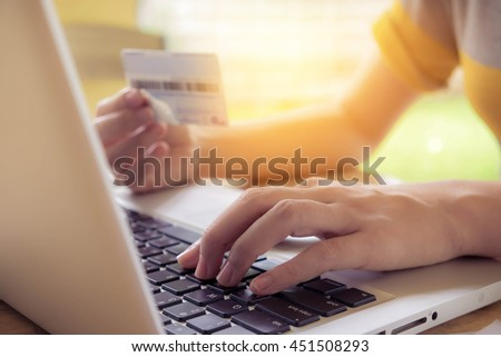Online payment, Business women's hands holding a credit card and using laptop for online shopping with morning light. vintage filter effect.