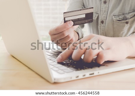 Online payment,Man's hands holding a credit card and using laptop for online shopping with vintage filter effect