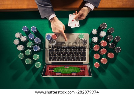 Online player's hands with laptop and stack of chips all around on green table top view, he is holding two ace cards - stock photo