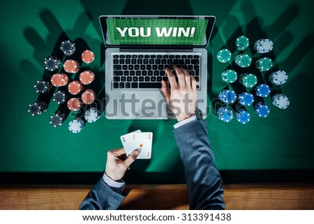 Online player's hands with laptop and stack of chips all around on green table top view, he is typing and holding two aces - stock photo