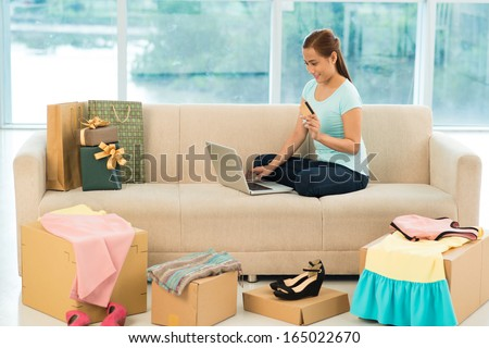 Online shopper sitting comfortably among her recent purchases - stock photo