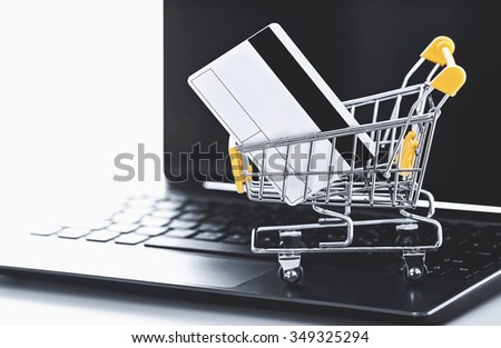 online shopping (a shopping cart with credit card on laptop) - stock photo