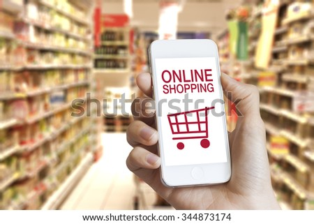 Online shopping application on mobile phone screen with grocery store in the background - stock photo