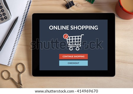 Online shopping concept on tablet screen with office objects on wooden desk. All screen content is designed by me. View from above. - stock photo
