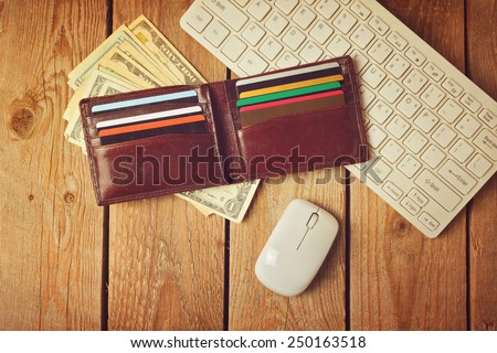 Online shopping concept with wallet, money and keyboard. Retro filter effect - stock photo
