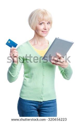 Online shopping. Happy aged woman holding credit card while using tablet computer. Isolated on white.