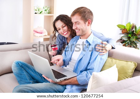 Online Shopping. Happy Smiling Couple Using Credit Card to Internet Shop on-line. Young couple with Laptop Computer and Credit Card buying online. Christmas and New Year Gifts. e-shopping - stock photo