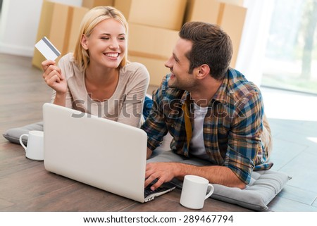 Online shopping makes life easier. Smiling young couple laying on the floor of their new apartment and shopping through Internet while cardboard boxes laying in the background - stock photo