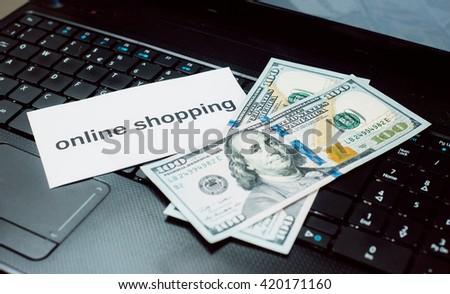 Online shopping. Money on the laptop keyboard. - stock photo