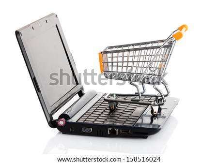Online shopping. Shopping cart with notebook on the white. shopping cart over a laptop - stock photo