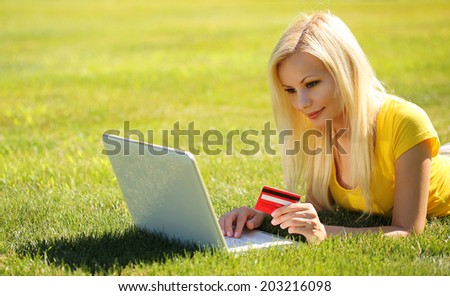 Online Shopping. Smiling Blonde Girl with Laptop using Credit Card and Lying Green Grass.  - stock photo