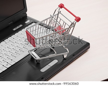 Online shopping. trolley on laptop isolated on white - stock photo