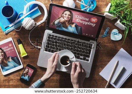 Online shopping website on laptop screen with female hands holding a coffee - stock photo