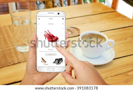 Online shopping with smart phone. Phone in woman hand. Buying women shoes on online store. Relax time with coffee on table. - stock photo